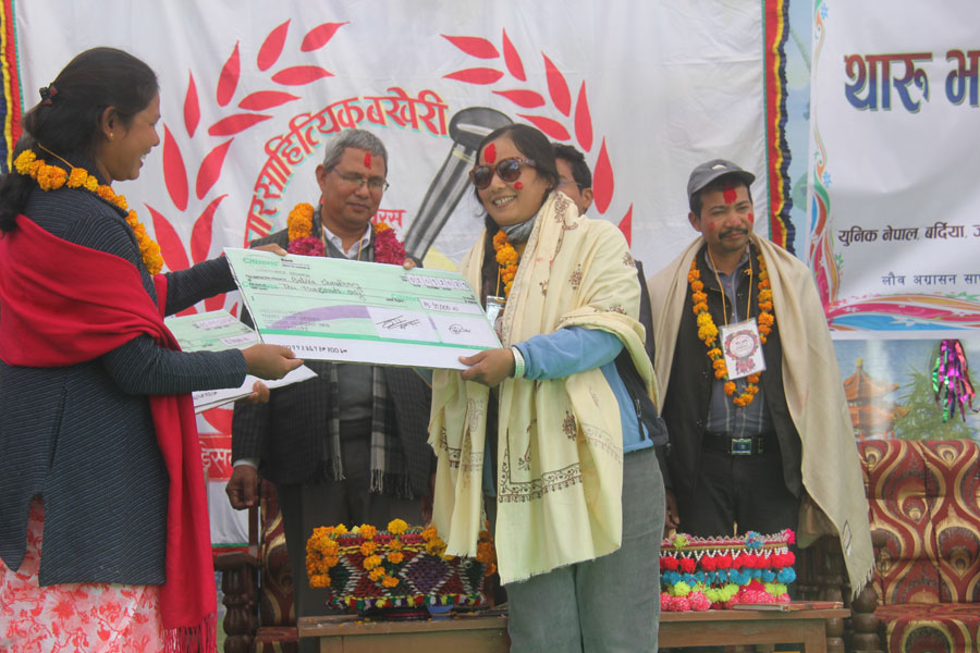 Tharu Female Writer - Balika Chaudhary receiving award from Tharu Home Resort Owner